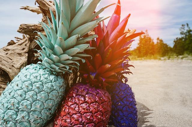 trois ananas dans la rue, un bleu turquoise, un rouge et un violet.